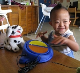 Boy standing by a simple switch that operates a toy dog facing towards camera