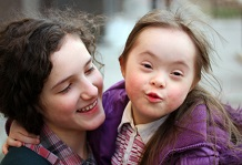 girl with Down Syndrome looking at the camera while being held by another girl who is looking at her