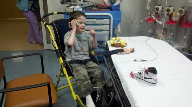 boy in wheeled chair engaging in adaptive play in a medical-setting