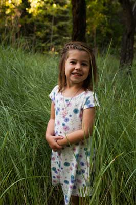 Young girl with autism happy in tall grass in her pretty dress