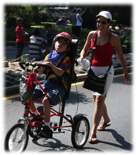 Mother following son, riding an adaptive tricycle